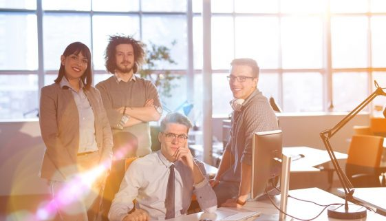 Group of successfull business group meeting in the at work with sun flare