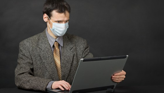 Person with medical mask working in Internet