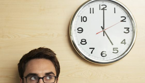Young businessman wearing spectacles looking at clock on wooden wall in office