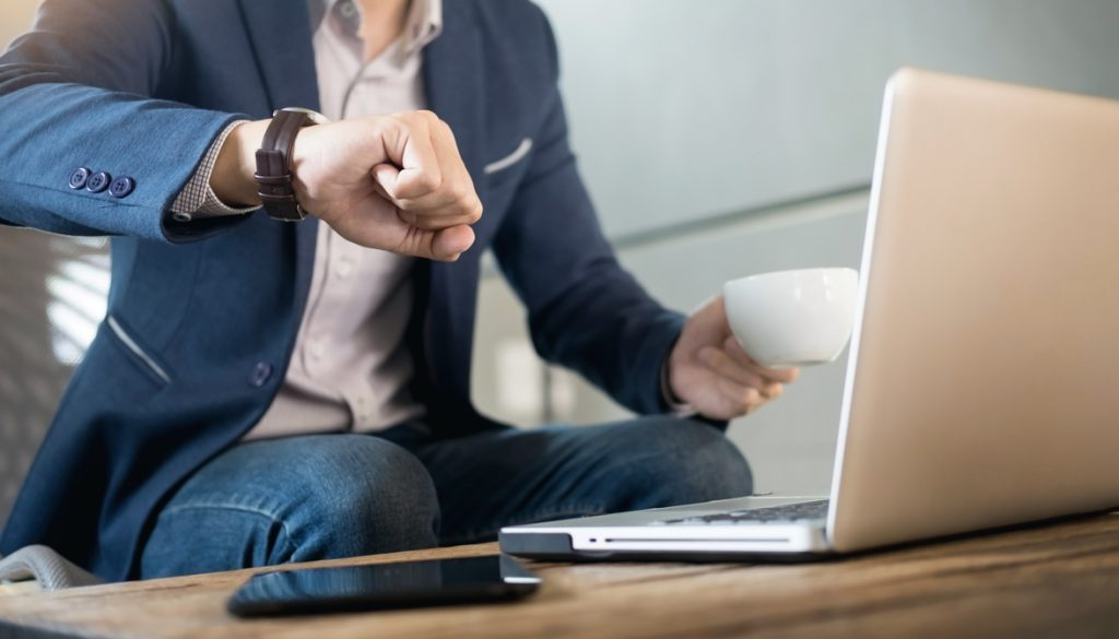 Handsome young businessman working at laptop with cup of coffee