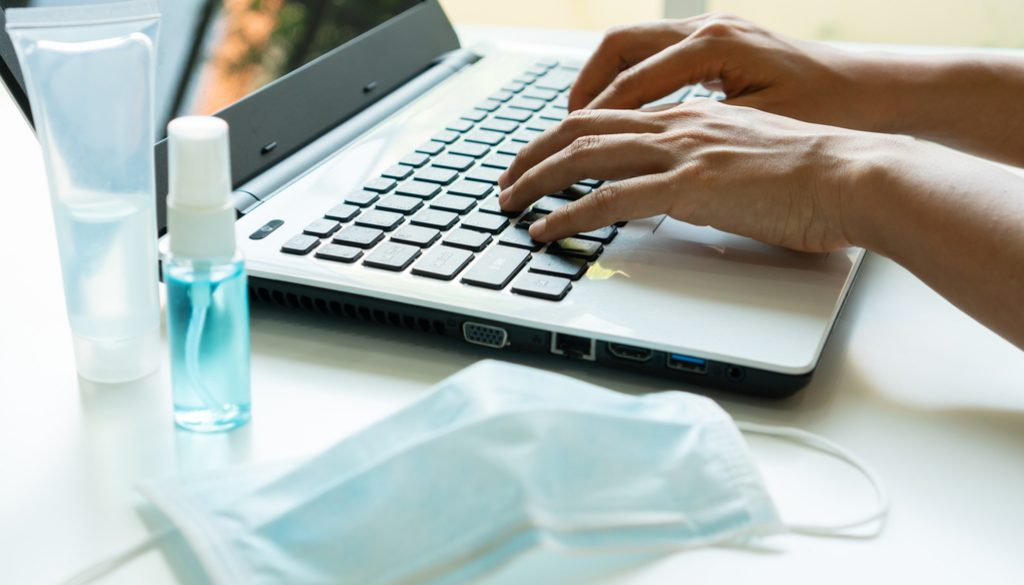 Close up of woman hands using laptop with sanitizer, alcohol spr