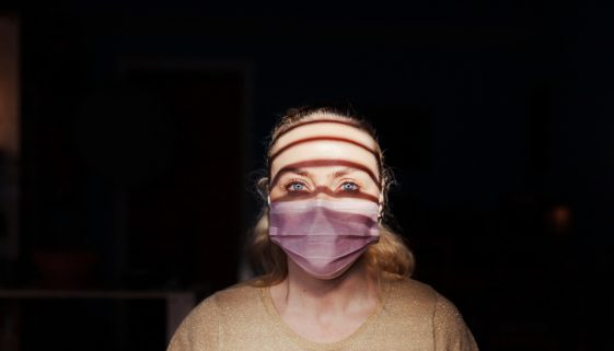 Woman wearing a surgical mask during quarantine in her houses