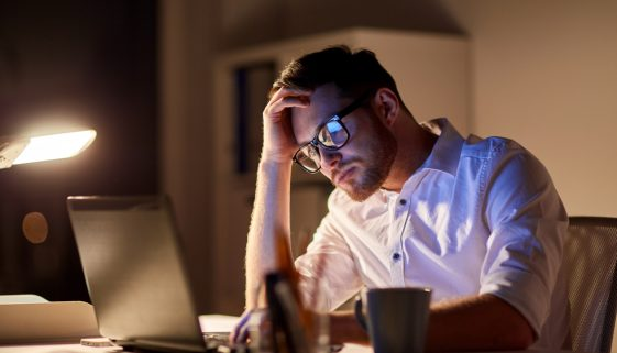 businessman with laptop thinking at night office