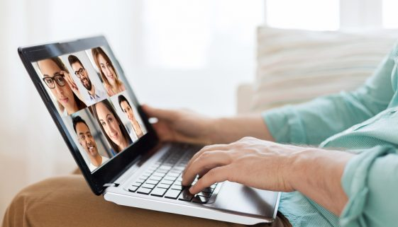 man with laptop having video call with colleagues