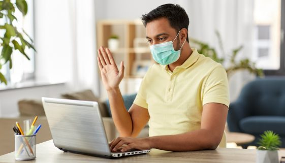 man in mask with laptop having video call at home