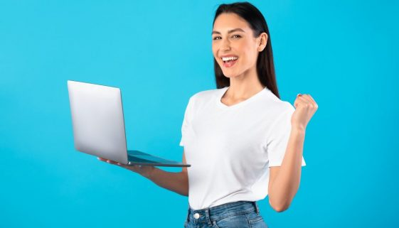 Happy female model celebrating win holding laptop
